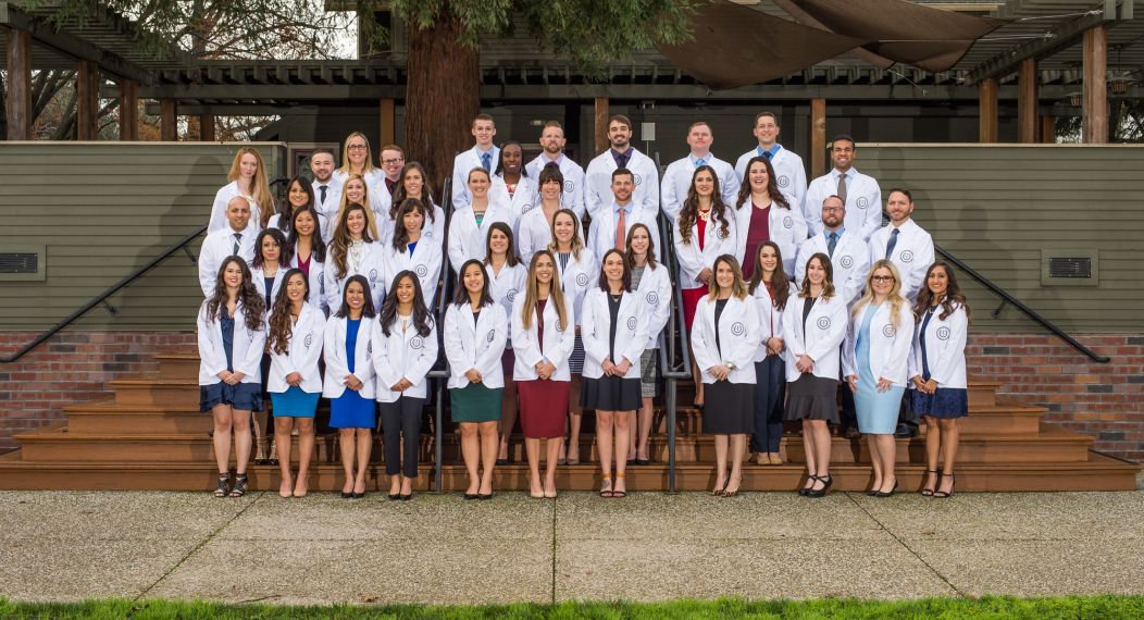 physician assistant students pose in their white coats